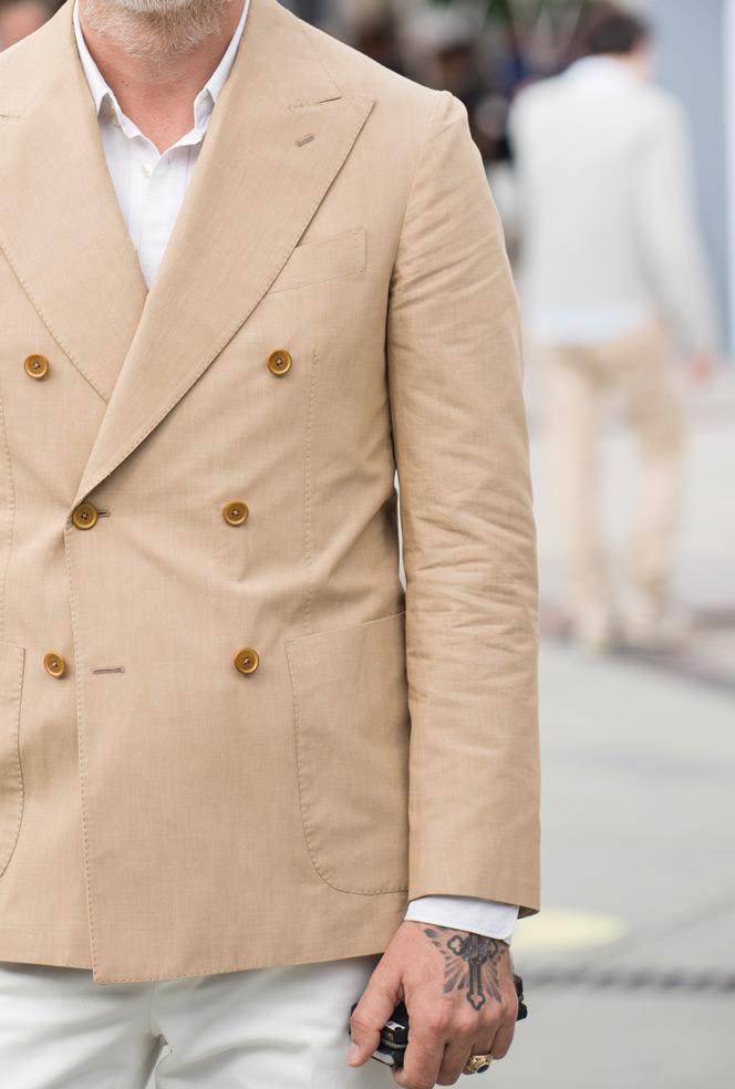 Nærbillede af beige dobbeltradet jakke.