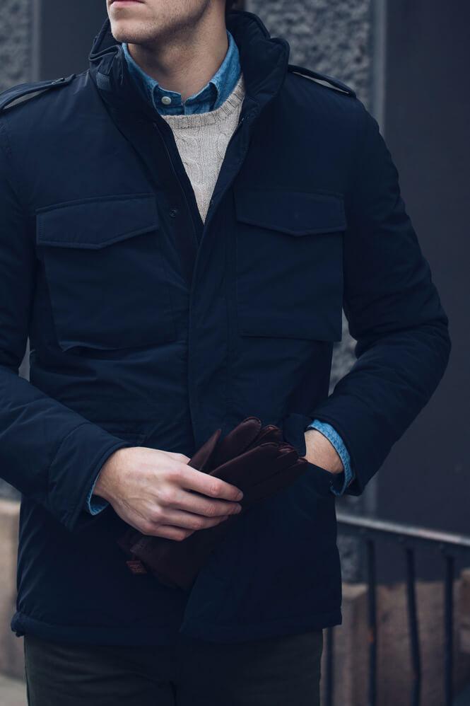 Närbild på outfit med blå jacka