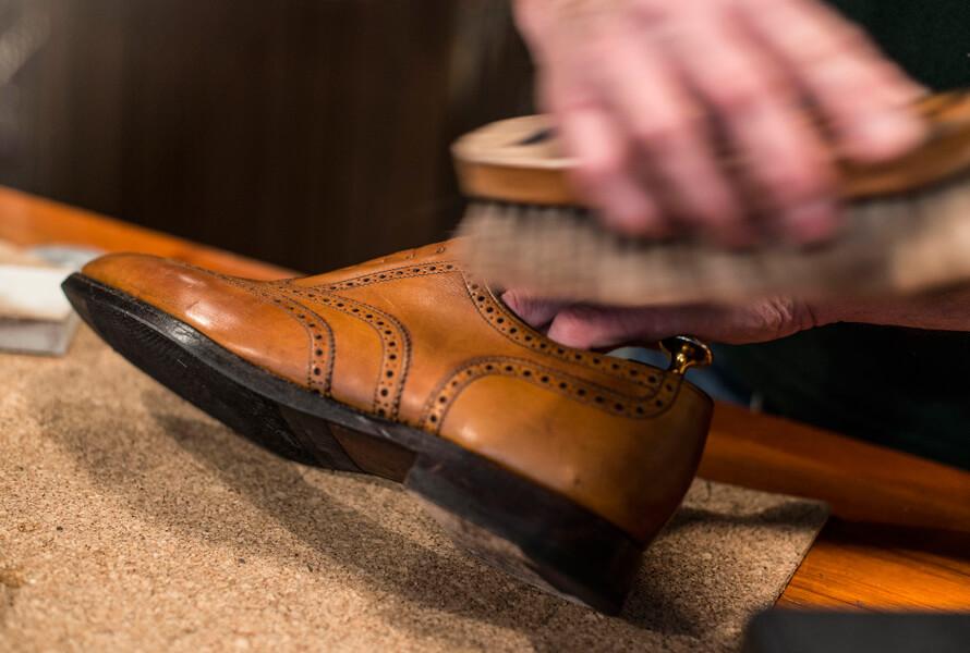 Skomaker som børster sko behandlet med Saphir Creme Pommadier 1925