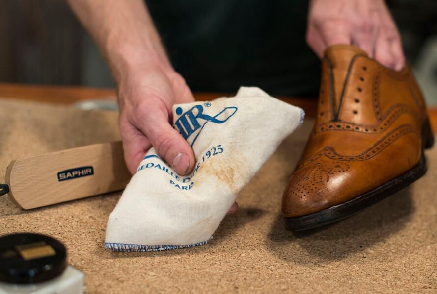Tørker av gammel krem og annet fra skoen med skinnrengjøring