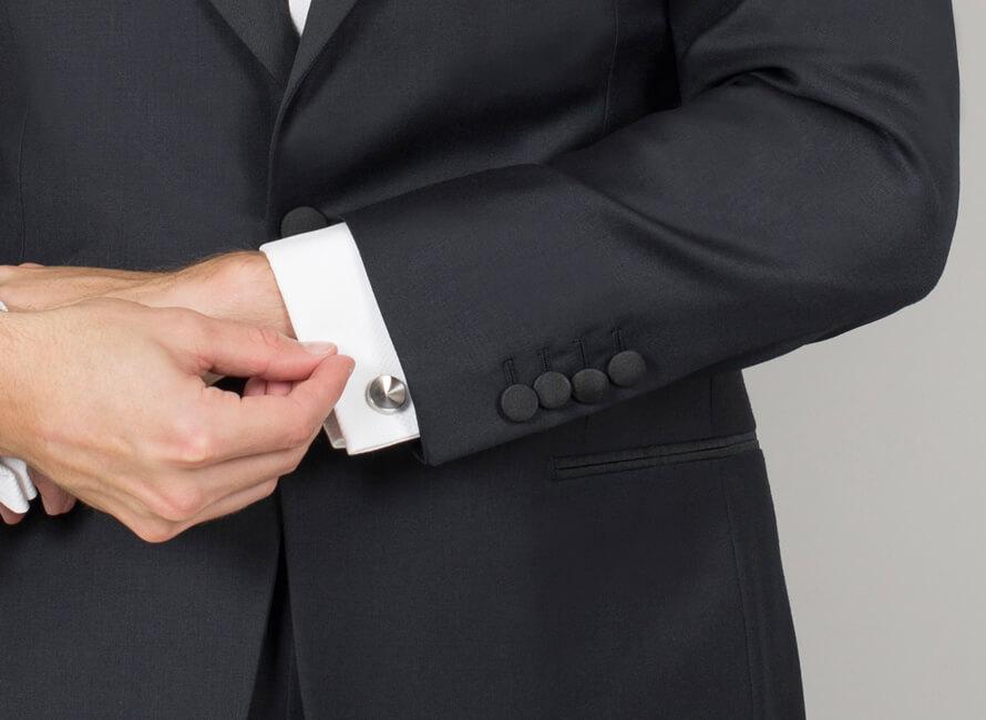 Närbild på manschettknappar i vit metall